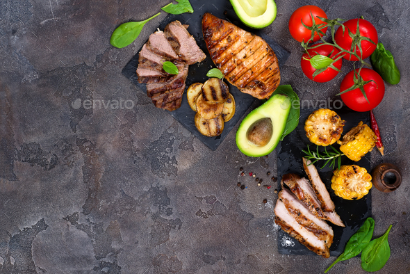 Fresh three types of grilled steak on slate plate with herbs, tomato, avocado and grilled potatoes - Stock Photo - Images