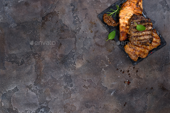 Fresh three types of grilled steak (chicken, pork, beef) on slate plate with herbs - Stock Photo - Images