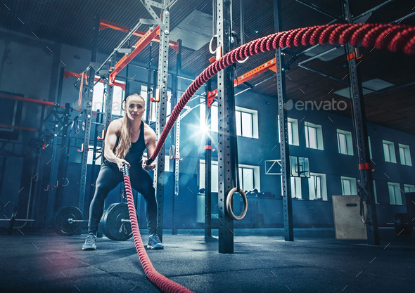 Woman with battle rope battle ropes exercise in the fitness gym. - Stock Photo - Images