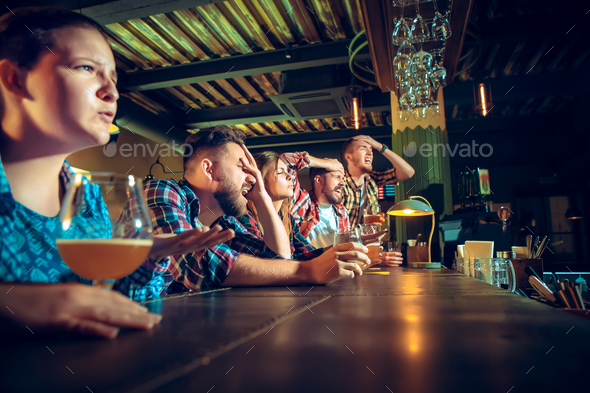 Upset male and female friends watching sport game or football match and drinking beer at bar or pub. - Stock Photo - Images