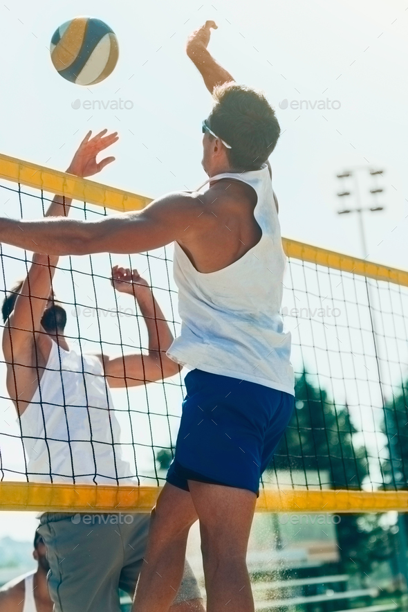 Male beach volleyball players jupming to hit the ball - Stock Photo - Images