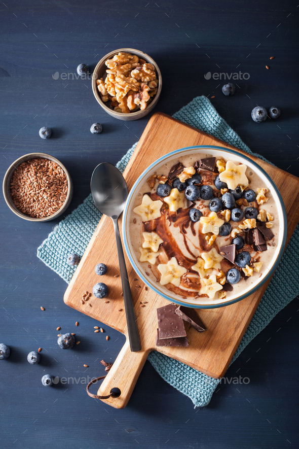 healthy banana smoothie bowl with blueberry chocolate walnuts - Stock Photo - Images
