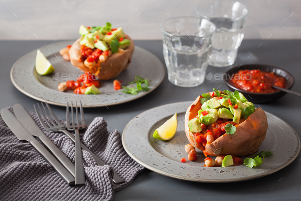 baked sweet potatoes with avocado chili salsa and beans - Stock Photo - Images