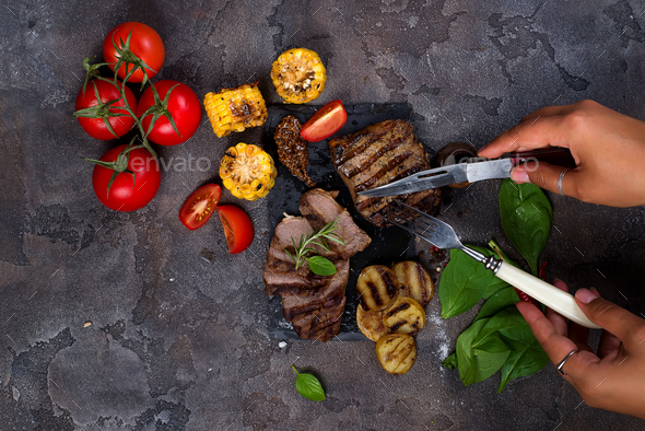 Female hands with a fork and knife cut Beef steak - Stock Photo - Images