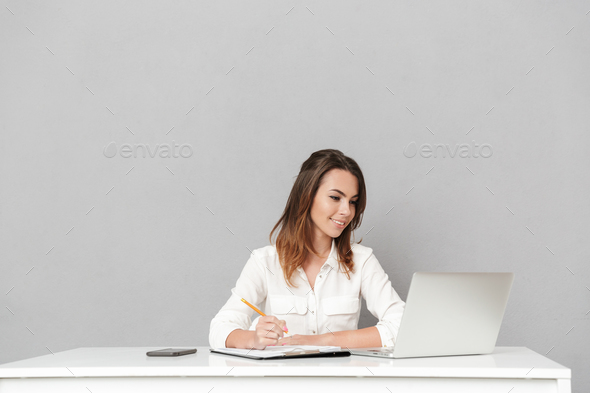 Amazing cheerful young business woman using laptop computer writing notes. - Stock Photo - Images