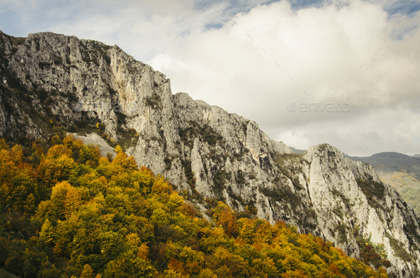 Mountain peak with colorful autumn trees and cloudy sky - Stock Photo - Images