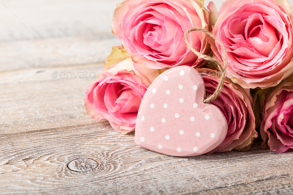 Fresh pink roses and heart decoration on wooden boards - Stock Photo - Images