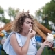 Video Portrait of Pretty Woman with Curly Hair Eats Cotton Candy and Smiles at the Amusement Park - VideoHive Item for Sale