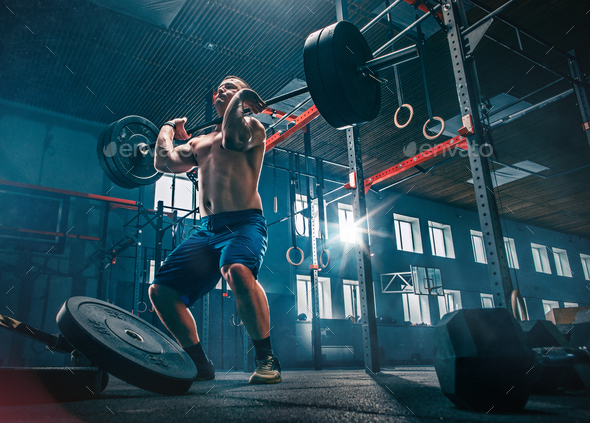 Fit young man lifting barbells working out in a gym - Stock Photo - Images