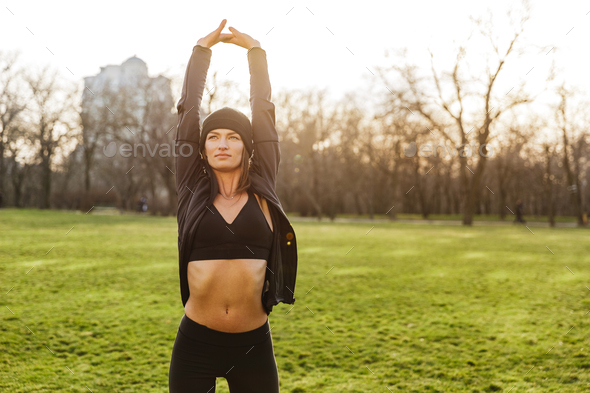 Image of attractive sportswoman in tracksuit, raising arms and s - Stock Photo - Images
