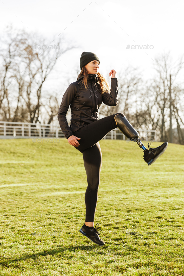 Image of energetic handicapped sportswoman in tracksuit, warming - Stock Photo - Images
