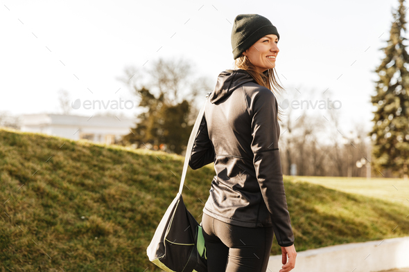 Photo of joyous athletic girl in black sportswear, walking with - Stock Photo - Images