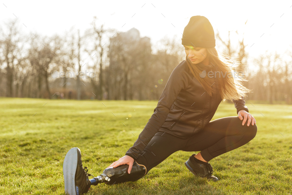 Photo of concentrated disabled girl in sportswear, doing sport e - Stock Photo - Images