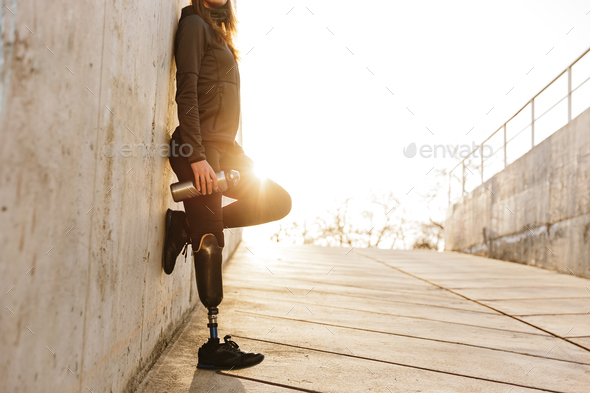 Cropped photo of handicapped woman with prosthesis leg in sports - Stock Photo - Images