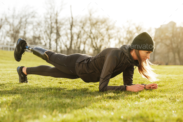 Image of sporty handicapped woman in black tracksuit, warming up - Stock Photo - Images