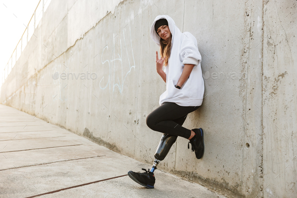 Photo of joyful disabled girl with bionic leg in casual wear, st - Stock Photo - Images