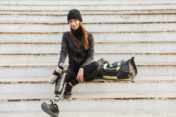 Photo of smiling handicapped woman in sportswear with prosthetic - Stock Photo - Images