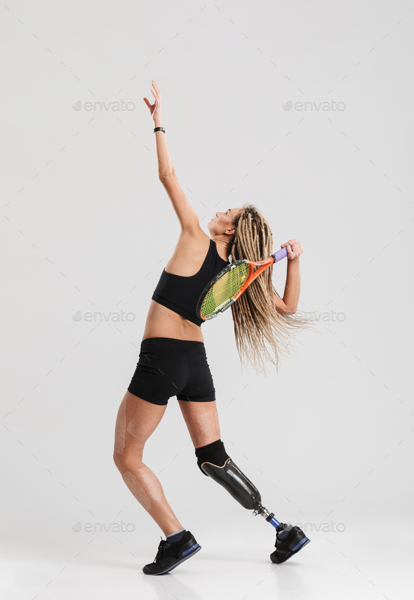 Tennis player standing isolated over grey background - Stock Photo - Images