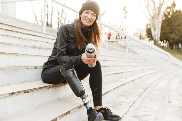 Strong willed handicapped woman in black tracksuit with prosthet - Stock Photo - Images