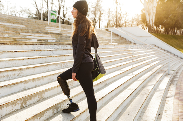 Image of disabled running girl with prosthetic leg in sportswear - Stock Photo - Images