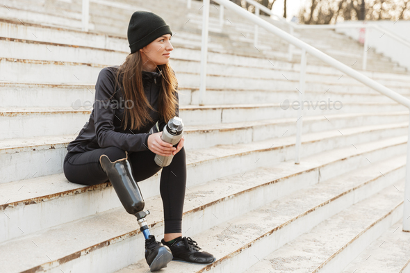 Portrait of attractive handicapped woman in black tracksuit with - Stock Photo - Images