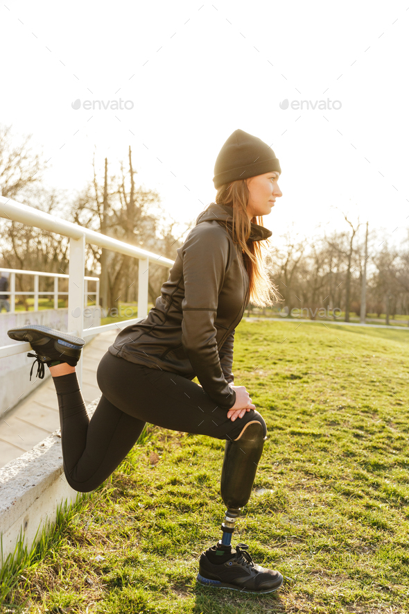 Photo of disabled running woman in sportswear, squatting and str - Stock Photo - Images
