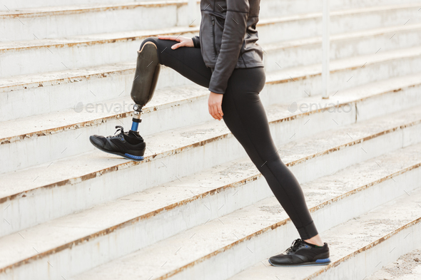 Cropped image of disabled running girl with prosthetic leg in sp - Stock Photo - Images