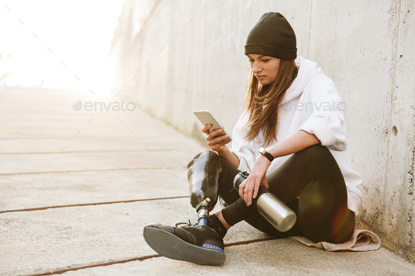 Photo of pretty young handicapped woman in streetwear having bio - Stock Photo - Images
