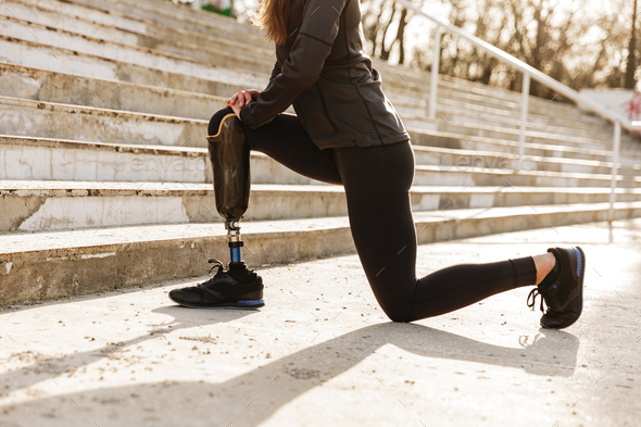 Cropped image of disabled sporty woman in tracksuit, doing sport - Stock Photo - Images