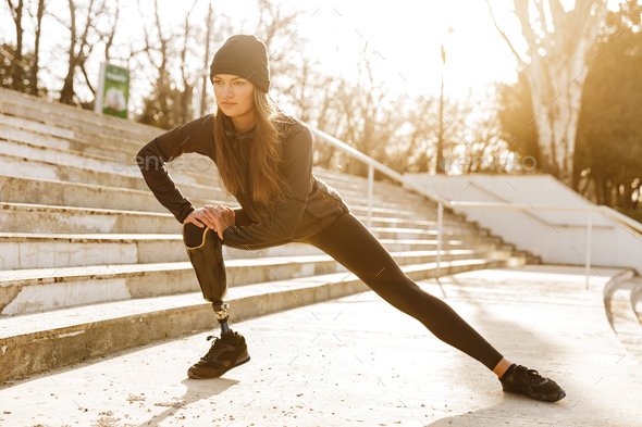 Image of disabled athletic girl in sportswear, doing sit ups and - Stock Photo - Images