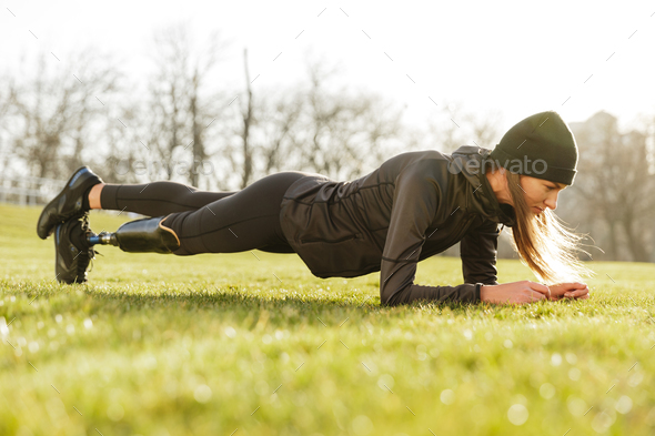 Image of athletic handicapped woman in black tracksuit, doing pl - Stock Photo - Images