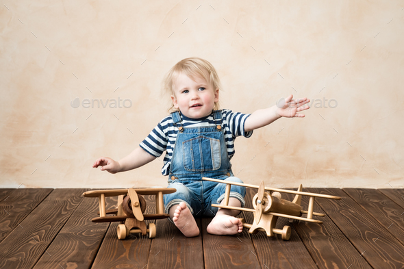 Happy child playing with toy airplane - Stock Photo - Images