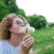 Attractive Woman in Sun Glasses Blows the Dandelions and They Fly Away on the Wind - VideoHive Item for Sale