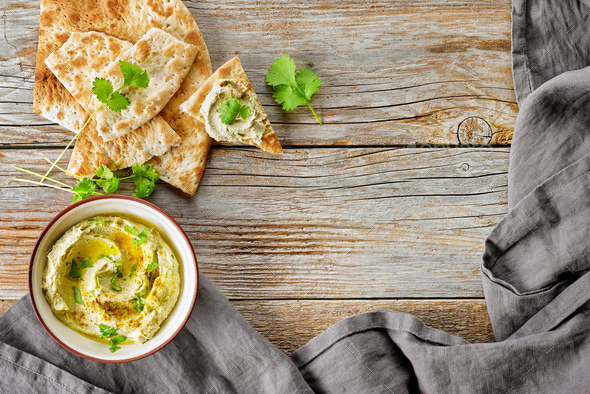 bowl of hummus on wooden table - Stock Photo - Images