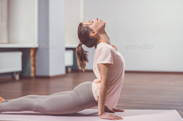 Young girl practicing yoga in class - Stock Photo - Images
