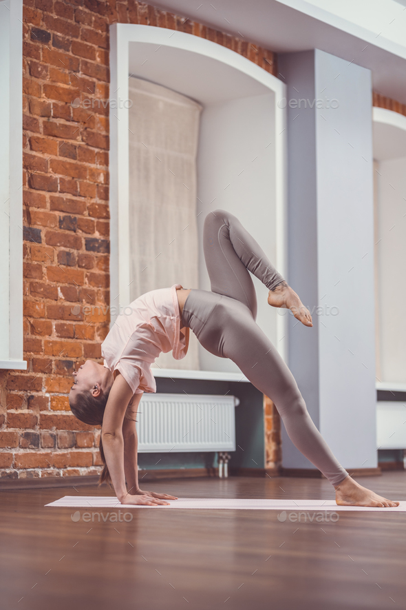 Training young girl in yoga studio - Stock Photo - Images