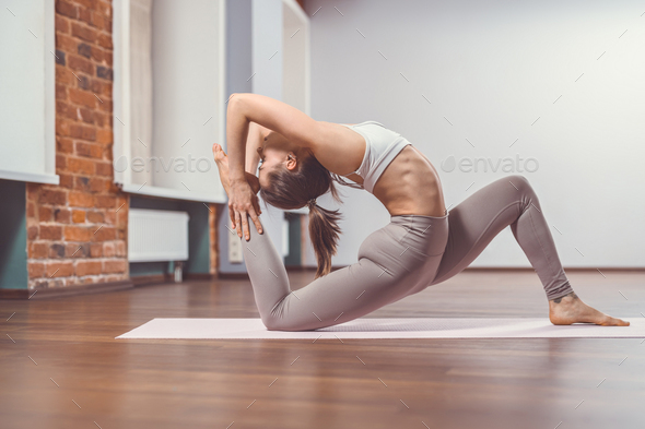 Young girl practicing yoga indoors - Stock Photo - Images