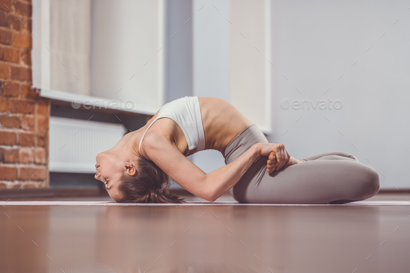 Young girl practicing yoga on the floor - Stock Photo - Images