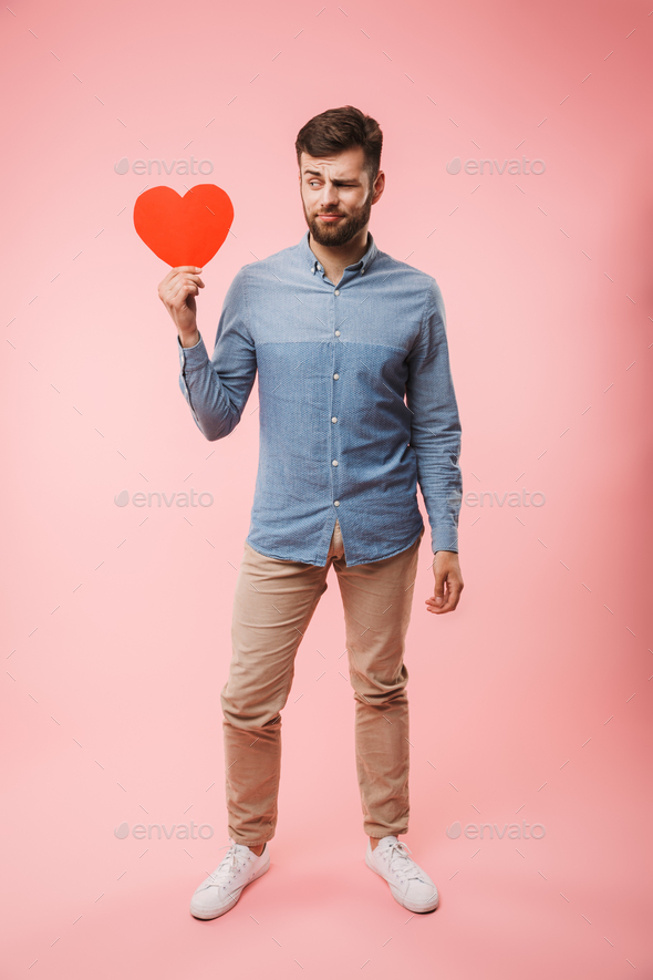 Full length of a confused young man holding red heart - Stock Photo - Images