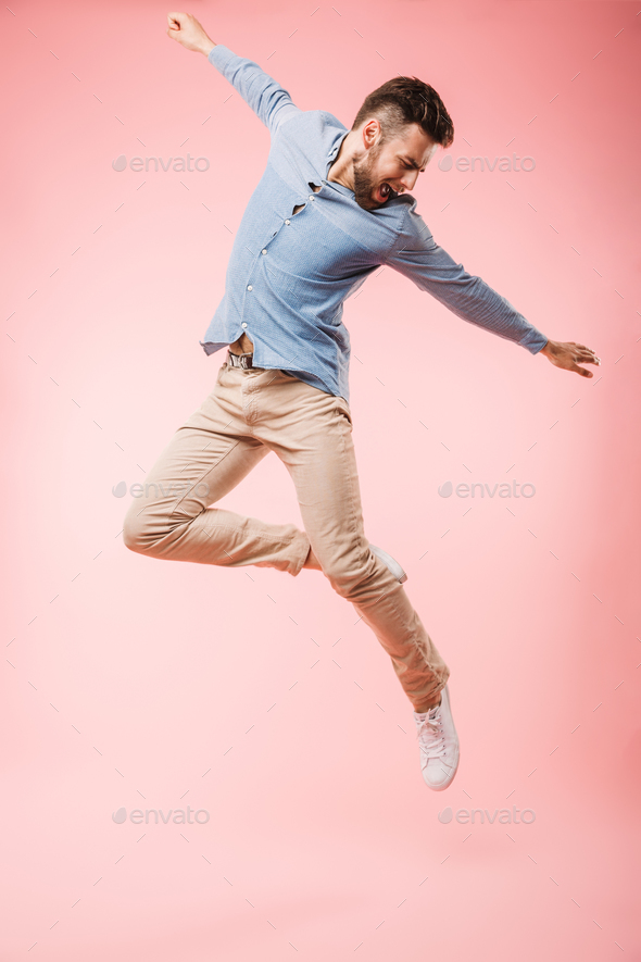 Full length of a cheerful young man jumping - Stock Photo - Images