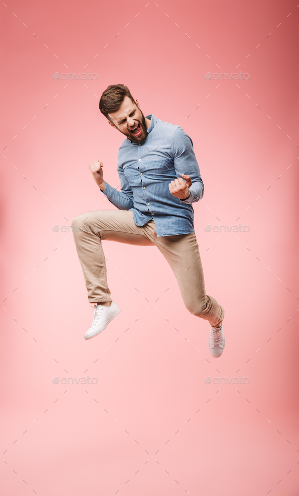 Full length of a satisfied young man jumping - Stock Photo - Images