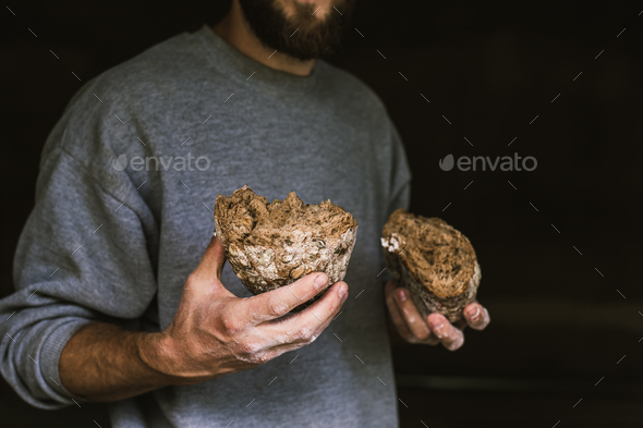 Baker man holding a rustic organic loaf of bread in his hands - Stock Photo - Images