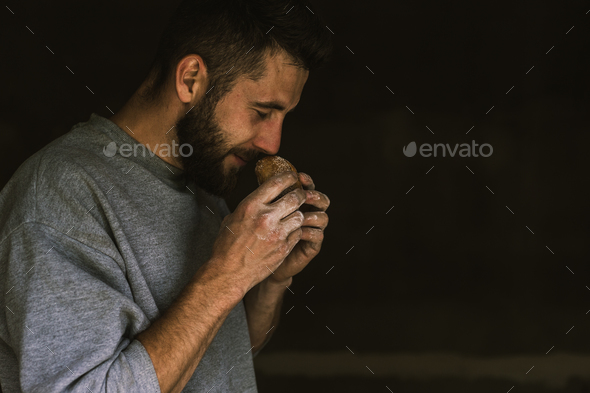 Close up of a young bearded man smelling delicious freshly baked bread - Stock Photo - Images