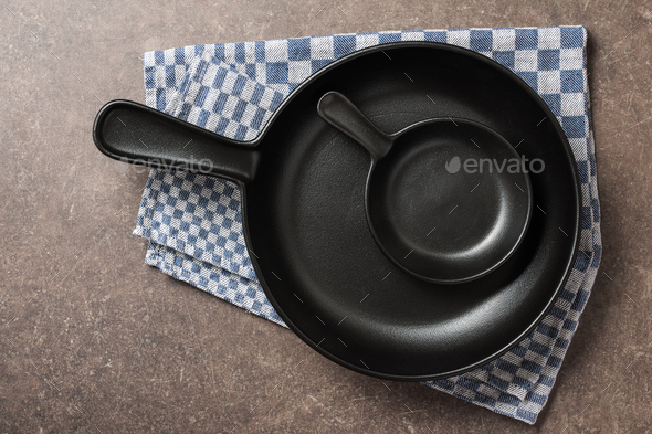 Big and small frying pans on kitchen table - Stock Photo - Images