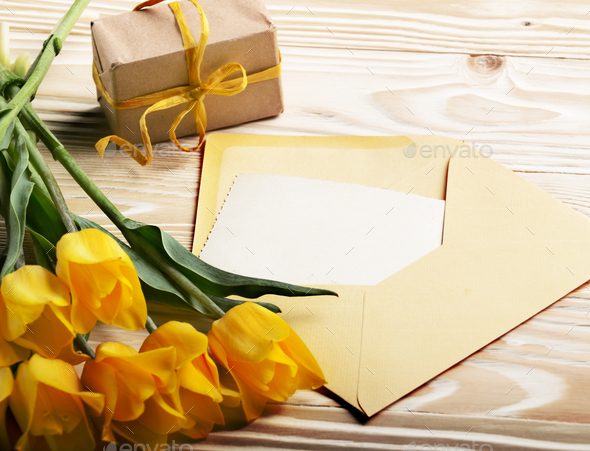 Yellow tulips near blank greeting card gift box and envelope on - Stock Photo - Images