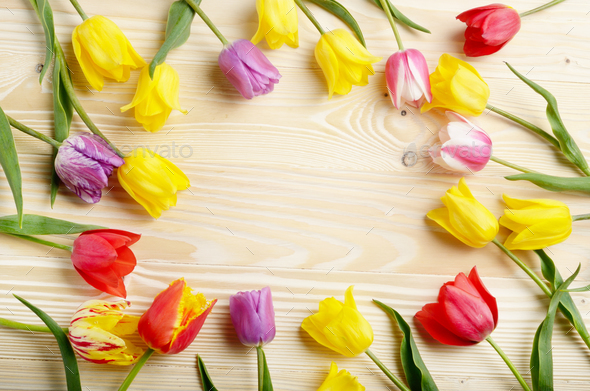 Frame of colorful tulips on natural wooden background with space - Stock Photo - Images