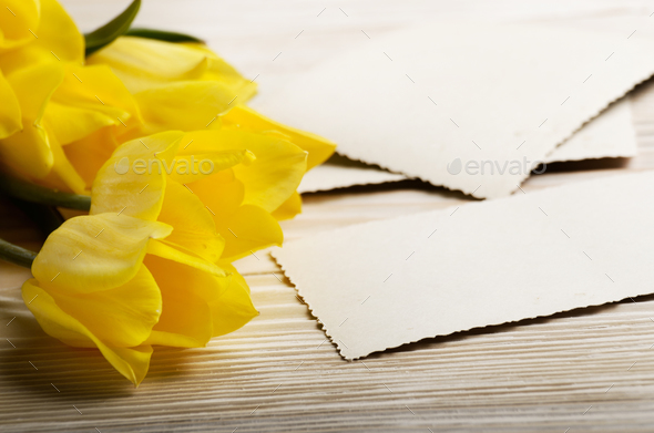 Yellow tulips and blank greeting card on natural wooden backgrou - Stock Photo - Images
