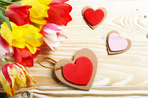 Colorful tulip flowers and heart shape cards on wooden table bac - Stock Photo - Images
