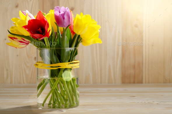 Bunch of Colorful tulip flowers in glass vase on wooden table ba - Stock Photo - Images