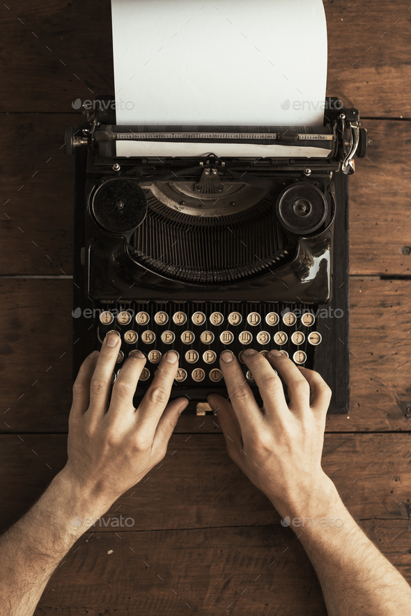 Young man's hands typing on an antique vintage typewriter - Stock Photo - Images